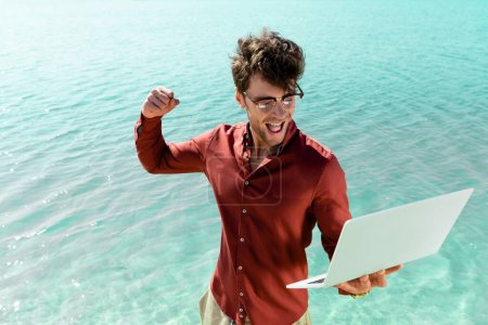 Photo for Excited handsome freelancer with laptop standing in turquoise water - Royalty Free Image