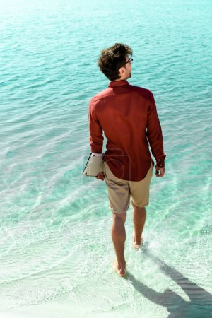 Photo for Back view of freelancer with laptop standing in turquoise water - Royalty Free Image