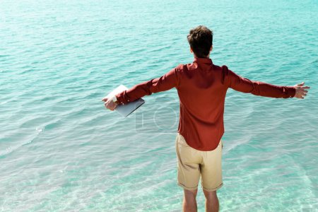 Photo pour Back view of freelancer with laptop in outstretched hands standing in turquoise water - image libre de droit