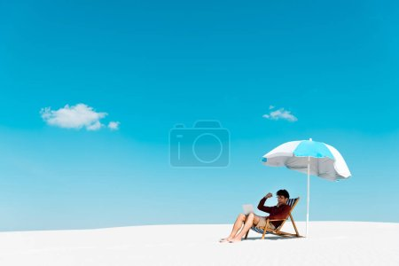 Photo for Freelancer sitting with laptop in deck chair under umbrella on sandy beach against blue sky - Royalty Free Image