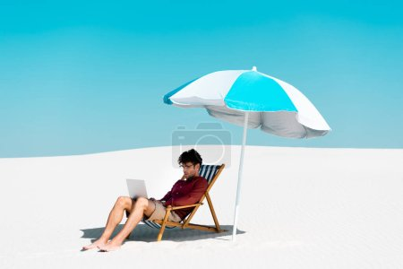 freelancer sitting with laptop in deck chair under umbrella on sandy beach against blue sky