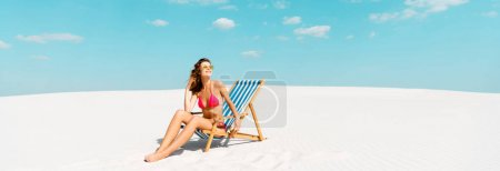 Photo for Smiling beautiful sexy girl in swimsuit and sunglasses sitting in deck chair on sandy beach with blue sky and clouds, panoramic shot - Royalty Free Image