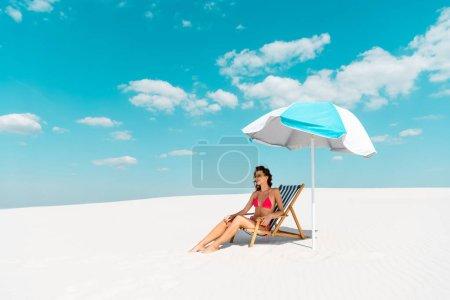 Photo pour Sourire belle fille sexy en maillot de bain et lunettes de soleil assis dans la chaise longue sous le parapluie sur la plage de sable - image libre de droit