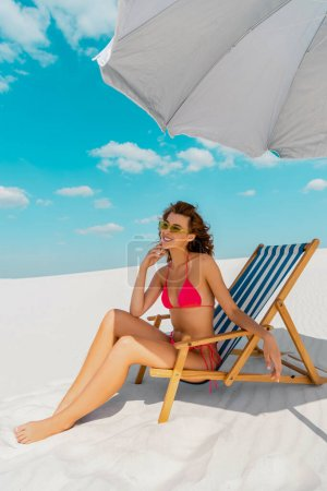 Photo pour Belle fille sexy souriante en maillot de bain et lunettes de soleil assise sur une chaise longue sous un parapluie sur une plage sablonneuse - image libre de droit