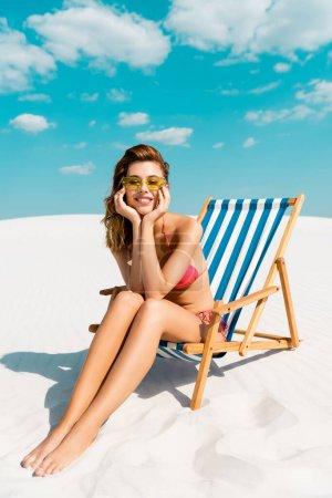 Photo pour Belle fille sexy souriante en maillot de bain et lunettes de soleil assise sur une chaise longue sur une plage de sable avec un ciel bleu et des nuages - image libre de droit