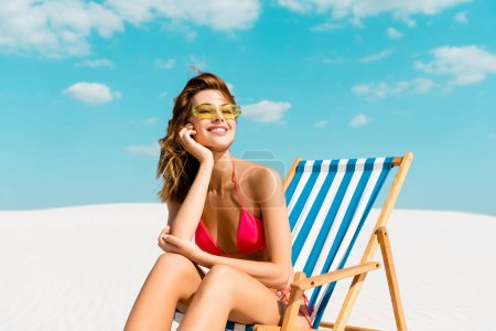Photo for Smiling beautiful sexy girl in swimsuit and sunglasses sitting in deck chair on sandy beach with blue sky and clouds - Royalty Free Image