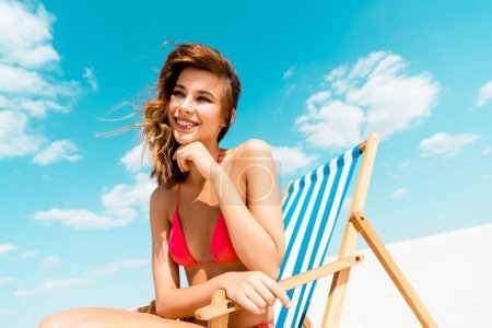 Photo for Smiling beautiful sexy girl in swimsuit sitting in deck chair on sandy beach with blue sky and clouds - Royalty Free Image