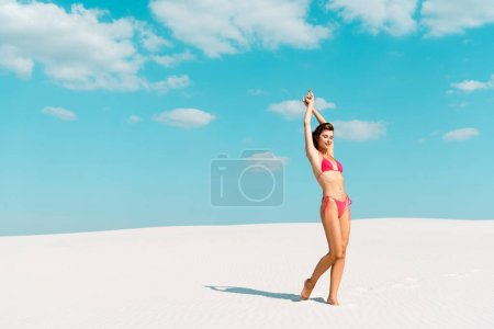 beautiful sexy girl in swimsuit with hands in air on sandy beach with blue sky and clouds