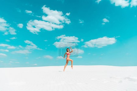 Photo pour Belle fille sexy en maillot de bain sautant sur une plage de sable avec un ciel bleu et des nuages - image libre de droit