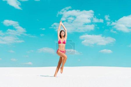 Photo pour Jolie fille sexy souriante en maillot de bain sautant avec les mains dans l'air sur une plage de sable avec ciel bleu et nuages - image libre de droit