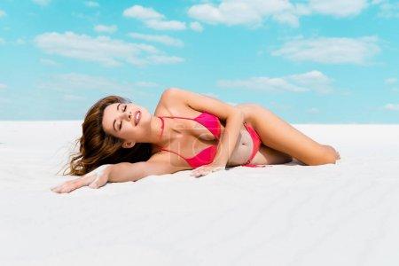 Photo pour Jolie fille sexy souriante en maillot de bain allongée sur une plage de sable avec un ciel bleu et des nuages en arrière-plan - image libre de droit