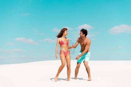 Photo pour Un jeune couple souriant tenant la main sur une plage de sable - image libre de droit