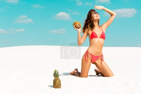 Photo for Smiling beautiful sexy girl in swimsuit with pineapples hiding from sun on sandy beach with blue sky and clouds - Royalty Free Image
