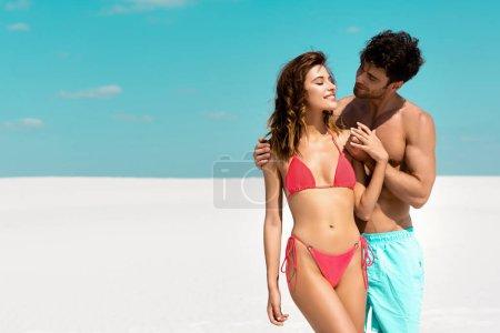 Photo pour Jeune homme embrassant sa belle copine sexy sur une plage de sable - image libre de droit