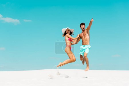 Photo for Smiling young couple jumping together on sandy beach - Royalty Free Image