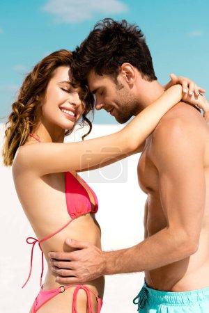 Photo pour Vue latérale d'un jeune couple souriant s'embrassant sur une plage de sable - image libre de droit