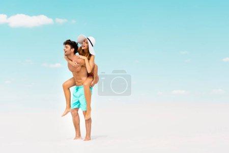 Photo pour Sourire jeune homme piggybacking petite amie sur la plage de sable - image libre de droit