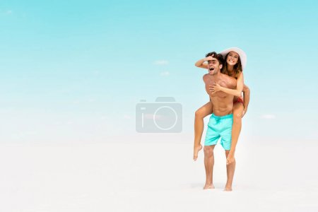 Photo for Smiling young man piggybacking girlfriend on sandy beach - Royalty Free Image