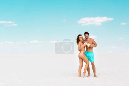 Photo pour Sourire jeune couple embrassant tout en tenant des boissons à la noix de coco sur la plage de sable - image libre de droit