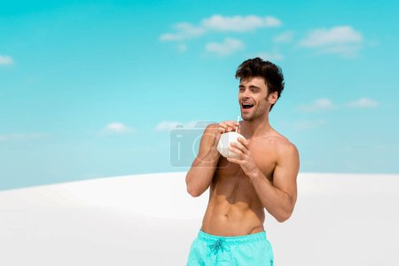 smiling sexy man with muscular torso in swim shorts with coconut drink on sandy beach