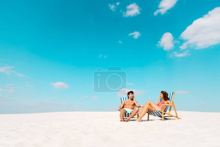 Photo for Smiling young couple sitting in deck chairs on sandy beach - Royalty Free Image