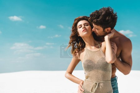 Photo for Young man kissing passionate sexy young girlfriend on beach - Royalty Free Image
