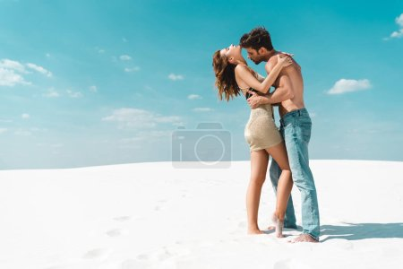 Photo for Side view of passionate sexy young couple embracing on beach - Royalty Free Image