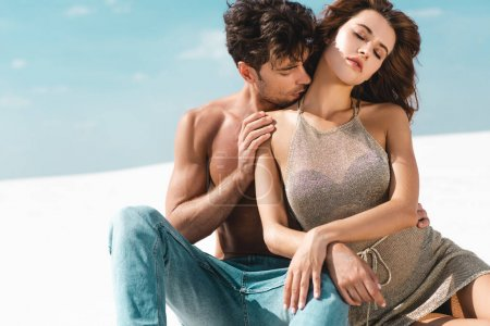 Photo for Passionate sexy young couple kissing on beach with closed eyes - Royalty Free Image