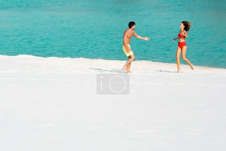 Photo for Young sexy couple running on sandy beach near ocean - Royalty Free Image