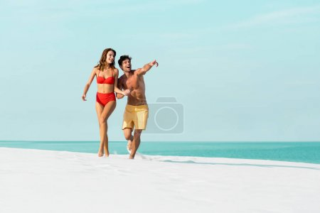 Photo pour Jolie jeune couple sexy courant sur une plage de sable et pointant vers l'océan - image libre de droit