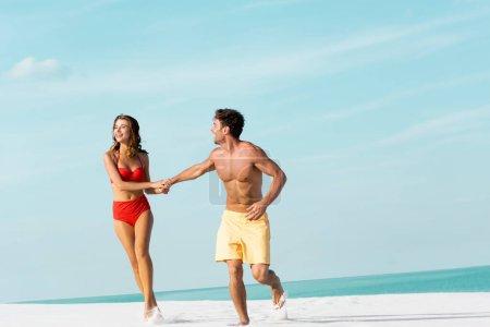 Photo pour Heureux jeune couple sexy courir sur la plage de sable près de l'océan - image libre de droit