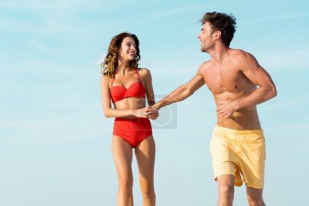 Foto de Feliz pareja sexy joven corriendo en el fondo del cielo azul - Imagen libre de derechos