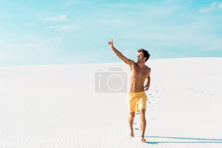 man in swim shorts with muscular torso walking on sandy beach