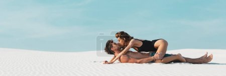 Photo for Side view of sexy young woman kissing and lying on boyfriend on sandy beach, panoramic shot - Royalty Free Image