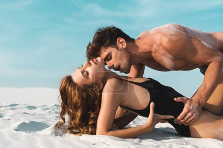 Photo for Sexy young man kissing girlfriend on sandy beach - Royalty Free Image