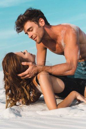 Photo pour Sexy jeune homme toucher petite amie sur la plage de sable - image libre de droit