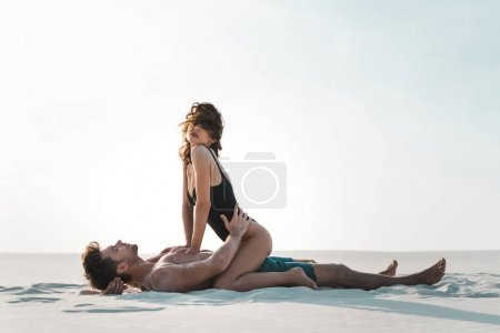 Photo for Side view of sexy passionate young couple lying on sandy beach - Royalty Free Image
