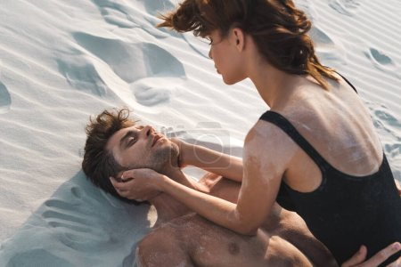 Photo for Sexy passionate young couple lying on sandy beach - Royalty Free Image