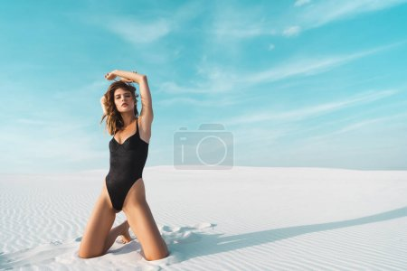 Photo for Sexy beautiful woman in black swimsuit posing on sandy beach with blue sky - Royalty Free Image