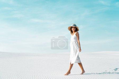 Photo pour Vue latérale de sourire belle fille en robe blanche et chapeau de paille marchant sur la plage de sable avec ciel bleu - image libre de droit