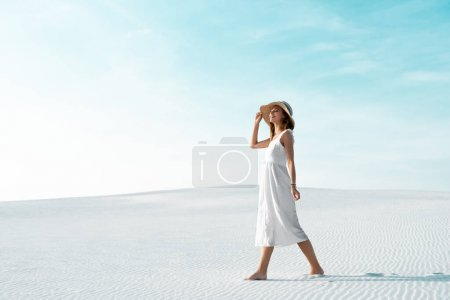 Photo for Side view of smiling beautiful girl in white dress and straw hat walking on sandy beach with blue sky - Royalty Free Image