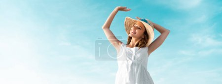 low angle view of smiling beautiful girl in white dress and straw hat against blue sky, panoramic shot
