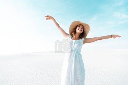 Foto de Hermosa chica feliz con vestido blanco y sombrero de paja con manos extendidas en la playa de arena con cielo azul. - Imagen libre de derechos