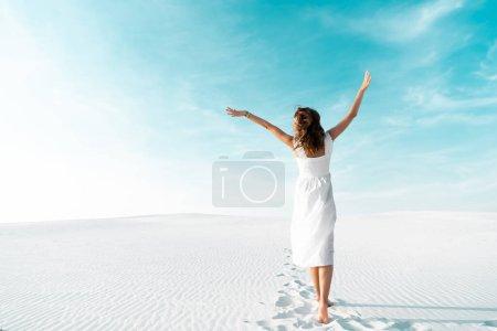 Photo pour Vue arrière de belle fille en robe blanche avec les mains dans l'air sur la plage de sable avec ciel bleu - image libre de droit