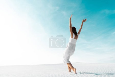 Photo for Beautiful girl in white dress with hands in air on sandy beach with blue sky - Royalty Free Image