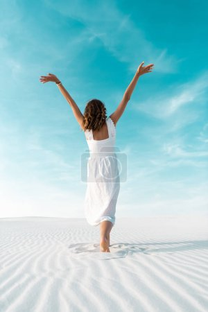 Photo for Back view of beautiful girl in white dress with hands in air on sandy beach with blue sky - Royalty Free Image
