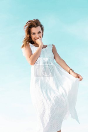 Photo for Low angle view of smiling beautiful girl in white dress against blue sky - Royalty Free Image