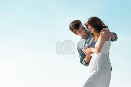 Photo pour Jeune couple étreignant contre le ciel bleu - image libre de droit