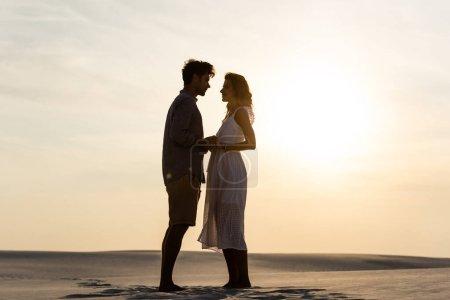Photo pour Vue latérale du jeune couple tenant la main sur la plage de sable au coucher du soleil - image libre de droit