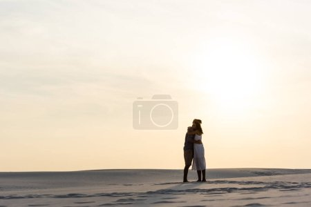Photo for Side view of young couple hugging on sandy beach at sunset - Royalty Free Image